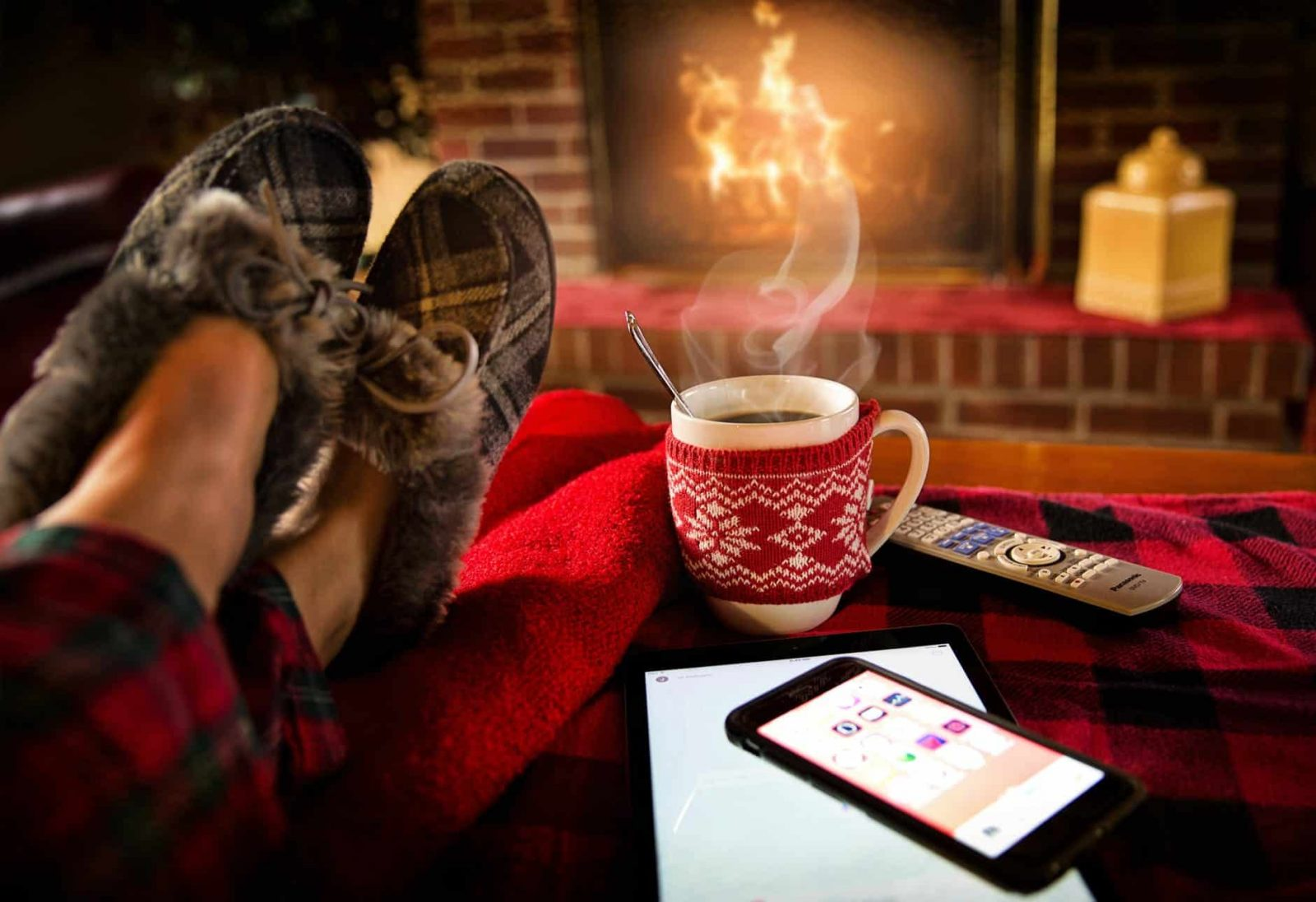 comfy woman's feet propped up before warm fireplace and hot drink